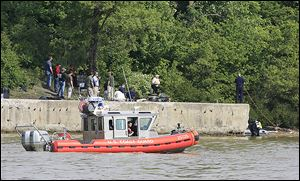 A Coast Guard boat cruises slowly up the Maumee River as Toledo Fire Department divers search for the missing girl Thursday.