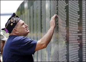 The half-size model of the Vietnam Veterans Memorial draws visitors to International Park in East Toledo, where it be through Sunday.