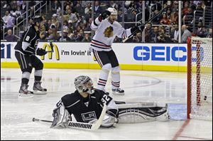 Chicago Blackhawks center Michal Handzus (26), of the Czech Republic, who got an assist, celebrates a goal by Marion Hossa against Los Angeles Kings goalie Jonathan Quick and defenseman Drew Doughty (8) in the the third period of Game 4.