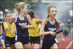 Napoleon's Sarah Waisner, right, takes the baton from Alexa Sonnenberg during the state championship meet Friday at Jesse Owens Memorial Stadium in Columbus, Ohio.