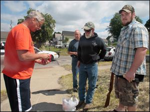 A Toledo resident, left, sells two long guns, shotgun shells and 7.62 ammo to three men who chose to not give their names. outside of the City's buyback program.