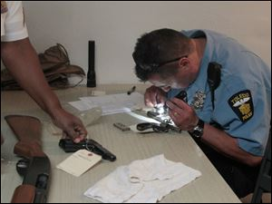 TPD officer Bill Michalski, right, records the manufacturer, caliber, and serial number of each weapon brought to the buyback.