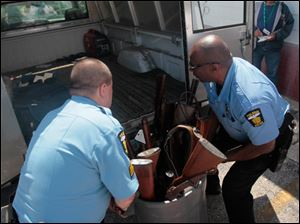 TPD officers Ed Mack, left, and Curtis Stone place a barrel of long guns that had been turned in to the city into a police vehicle. The barrel joined two crates of handguns the city had bought back.