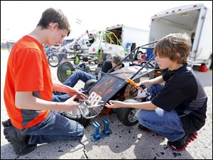 Anthony McCune, 15, left, Sylvania, and his friend Justin Garmenn, 16, center, Grand Rapids, Ohio, help fix the car of McCune's brother Matthew Dolinar, 13, right, Sylvania, between races.