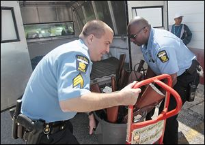 Officers Ed Mack, left, and Curtis Stone place a barrel of guns collected during the event into a police vehicle outside People's Missionary Baptist Church.