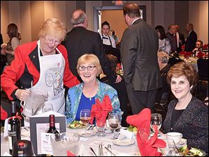 Central Catholic High School's Celebrity Wait Night chairmen Peg O'Hearn pours water for partygoes Jackie Black and Dee Weik.
