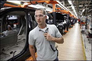 Jeff Caldwell, 29, a chassis assembly line supervisor, monitors the assembly line at the Chrysler Jefferson North Assembly plant in Detroit. The auto industry is on a hiring spree as car makers and parts suppliers race to find engineers, technicians and factory workers to build the next generation of vehicles.