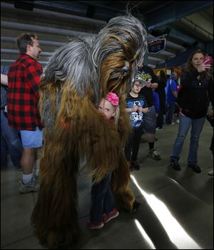 "Abby Kurdziel, 4, gets a hug from Chewbacca on the concourse before a Toledo Mud Hens game May 4. Transportation Security Administration agents in Denver briefly stopped ""Star Wars"" franchise actor Peter Mayhew, who plays Chewbacca, recently as he was boarding a flight with a cane shaped like one of science-fiction's most iconic weapons."