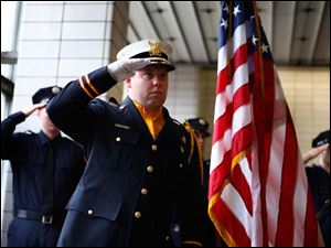 Firefighter Kyle Wiley salutes during the Toledo Fire Department memorial service at Fire Station No. 1 downtown.