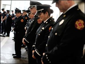 Firefighters bow their heads as a prayer is said in honor of those who have died in the line of duty.
