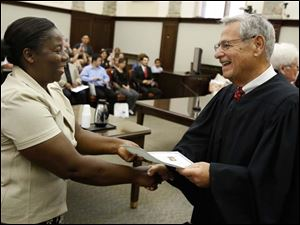 Yar Kiepeeh Davay of Toledo, originally from Liberia, gets her certificate of citizenship from Judge David Katz during a naturalization ceremony in U.S. District Court in Toledo. She and 27 other people became U.S. citizens Monday.