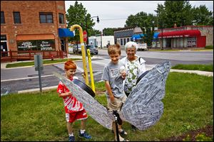 Molly Wachtmann of Whitehouse and her grandsons Luke Yokum, 9, left, and Matthew, 12, center, inspect a newly erected fiberglass butterfly in Whitehouse. The trio examined each butterfly in town.