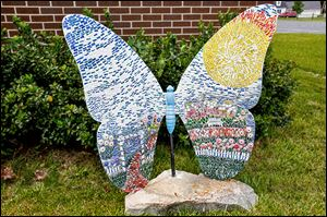 A newly erected mosaic and fiberglass butterfly stands near the DiSalle Real Estate building in downtown Whitehouse.