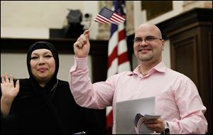 Houda Husamuldeen Albakri and her brother, Omar Albakri, both of Sylvania Township and originally from Iraq, wave to family after becoming U.S. citizens. Their mother, Elham Hasan Salami, also became a citizen during Monday's naturalization ceremony.