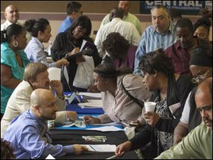 Job seekers inquire for positions at the 12th annual Mission career fair in the skid row area of Los Angeles last week.