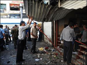 Syrians inspect a damaged shop at a scene of two explosions in the central district of Marjeh, Damascus today.