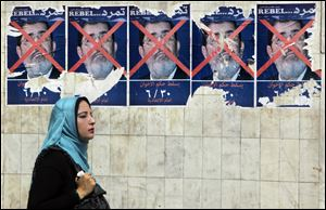 An Egyptian walks past anti-government posters for a campaign calling for the ouster of Egyptian President Mohammed Morsi and for early presidential elections in Cairo, Egypt.