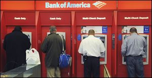 Customers use ATMs at a Bank of America branch office in Boston. A report by the Consumer Financial Protection Bureau released Tuesday said it's hard for consumers to anticipate and avoid overdraft charges. These charges vary widely from one bank to the next, the report said.