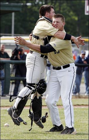 Perrysburg catcher Kyle Durham hugs pitcher Mark Delas after the Yellow Jackets beat Norwalk in the Division I district final.