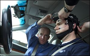 Russ Martin of AAA, is assisted by Joel Cooper, left, hooking the electroencephalographic (EEG)-configured skull cap to the research vehicle during a demonstrations in support of their new study on distracted driving in Landover, Md..