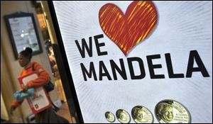 A shopper walks past a sign advertising a shop that sells commemorative coins with the face of Nelson Mandela in the Sandton City shopping centre in Johannesburg, South Africa.