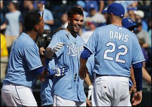 Kansas City Royals' Eric Hosmer, middle, gets covered with
