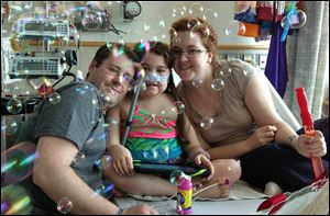Sarah Murnaghan, center, celebrates the 100th day of her stay in Children's Hospital of Philadelphia with her father, Fran, left, and mother, Janet, May 30.