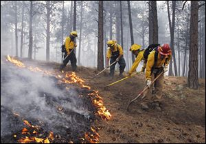 Black Forest Fire Dept. officers burn off natural ground fuel in an evacuated neighborhood, prepping the area for the encroachment of the wildfire in the Black Forest area north of Colorado Springs, Colo., on Wednesday.