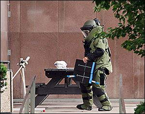 A Toledo police bomb squad member inspects a suspicious package on a table outside One Government Center.