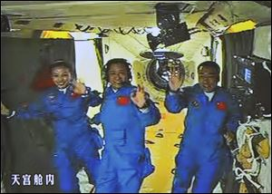 In this image made off the screen at the Beijing Aerospace Control Center and released by China's Xinhua News Agency, Chinese astronauts, from left, Wang Yaping, Zhang Xiaoguang and Nie Haisheng, wave inside the Tiangong-1 space module Thursday.
