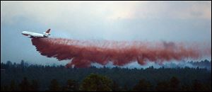 A DC-10 Air Tanker drops fire retardant near home in the evening as the Black Forest Fire continues to burn out of control for a second straight day near Colorado Springs on Wednesday.