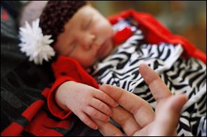 Columbus Grove, Ohio, resident Chad Bingley holds the hand of his newborn daughter, Kyra.