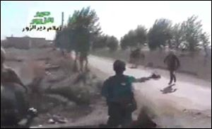 In this amateur video provided by a group which calls itself Ugarit News, Syrian rebels cross a road during a raid on the village of Hatla, Syria, Wednesday.