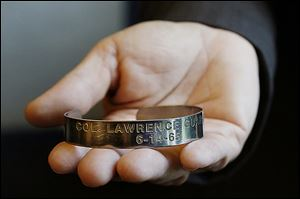 Patty James, the University of Toledo director of senior administrative operations, holds the POW bracelet, which reads: 'Col. Lawrence Guarino 6-14-65.'