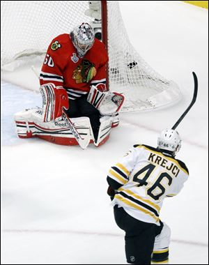 Chicago Blackhawks goalie Corey Crawford (50) makes a save on a shot by Boston Bruins center David Krejci (46) during the first period.