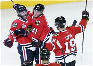 Chicago Blackhawks left wing Brandon Saad (20) celebrates with right wing Marian Hossa (81) and center Jonathan Toews (19) after scoring a goal during the second period Wednesday in Chicago.