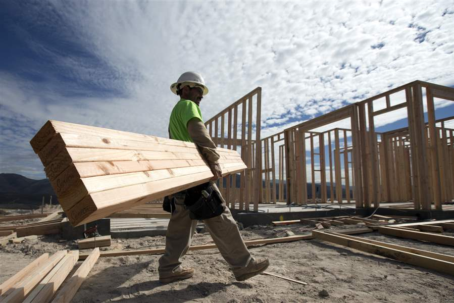 Construction-worker-Miguel-Fonseca-carries-lumber-as-he