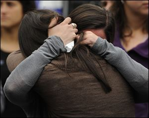 Carlee Soto, front, and Jillian Soto, sisters of slain teacher Victoria Soto, embrace during a ceremony on the six-month anniversary honoring the 20 children and six adults gunned down at Sandy Hook Elementary School.
