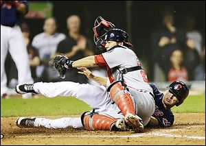 The Indians' Drew Stubbs, right, scores while the Nationals' Kurt Suzuki tries to make the play in the ninth inning.