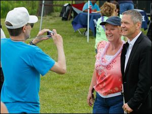 Lee Markham, Monroe, takes a photo of his wife Faye Markham as she poses with Michigan gubernatorial candidate Mark Schauer.