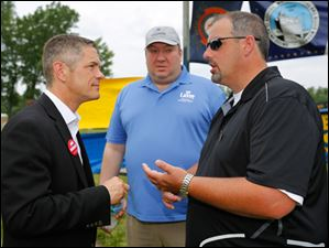Michigan gubernatorial candidate Mark Schauer, left, speaks with Bill LaVoy, 17th District State Representative, middle, and Dan Minton, Monroe County Democratic Party Chairman, right.