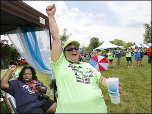 Debie Brakke of Adrian raises a cheer during the second annual Middle Class Survival Rally in Monroe on Saturday.