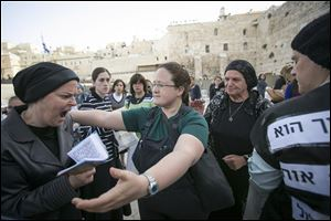An Israeli member of the Women of the Wall organization, right, tries to hug an ultra-Orthodox woman as they pray at the Western Wall.