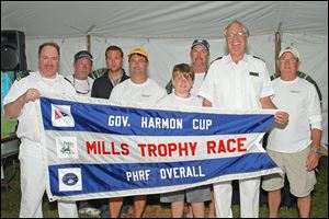 Rear commodore John Sokol, left, and vice commodore Tom Kaintz, second from right, present a flag to the winning crew of the Governor's Cup after the Mills Trophy Race. Crew members include, beginning second from left, Tom Morgan, Steve King, John Bollin, Robert Bollin, Joe DiMasso, and Bill Bollin, far right.