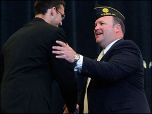 Whitmer High School rising senior Casey Holsten, left, shakes hands with Bob Oehlers after introducing him.