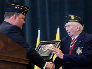 Bob Oehlers, a 1985 Whitmer High School alumnus and 1989 West Point graduate, honors Clinton Longenecker, a member of Conn-Weissenberger American Legion Post 587 in Toledo. Mr. Longenecker is an Army WWII veteran who participated in D-Day at Omaha Beach.