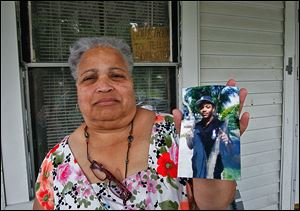 Linda Watson holds a photo of her nephew Frederick D. Watson, Jr., who was found shot to death in a car early Sunday morning.