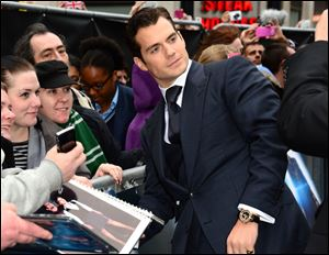 Actor Henry Cavill signs autographs for fans at the European premiere of 'Man Of Steel' in London on Wednesday.