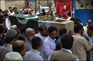 People carry the flag-wrapped casket of a high-ranking government official who was killed in Saturday's bombing at the Bolan Medical complex in Quetta, Pakistan, Sunday, June 16, 2013. The radical Lashkar-e-Jhangvi group claimed responsibility for the attacks on the hospital and a women's university bus.
