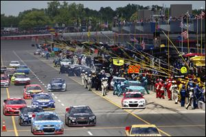 Cars exit pit road during a caution at the Quicken Loans 400. There were eight cautions in the race.